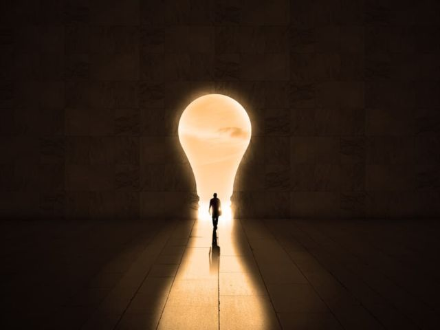 Businessman getting out from a dark room to financial freedom. Exit through a lightbulb door, business idea or startup inspiration concept